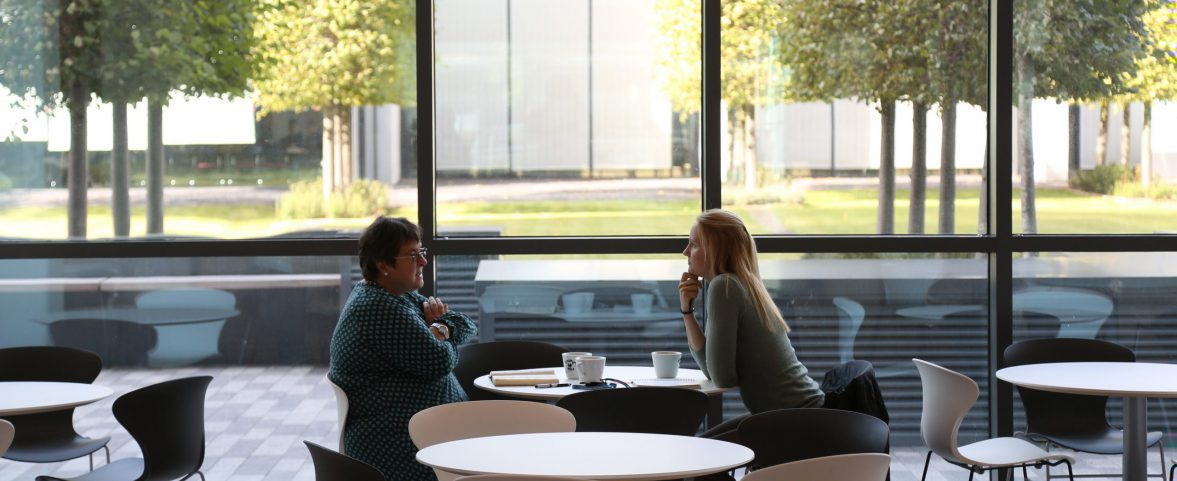 Photo of two people talking at a table in the JCBC cafe, against the large picture window